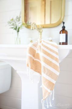 Save space by using a pedestal sink and make it feel larger by adding a long, vertical mirror.