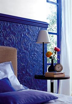 Tête de lit peinte en bleu klein fabriquée avec du papier peint 3D et baguettes moulure bois.