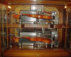 Two violins stacked vertically inside a 1918 Nickelodeon - Mills Novelty Double Violin Mechanical Machine