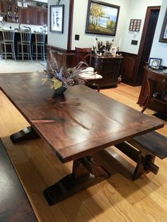 """This is another one of our BIG & Bold trestle tables. We call this one the """"French Colonial"""" Shown here with a thicker """"Rustic"""" Pine top, Tiger Maple Bread Board Ends, and a beautiful,rich dark stain to compliment it's luxurious surroundings. There are also two matching benches to complete the look."""