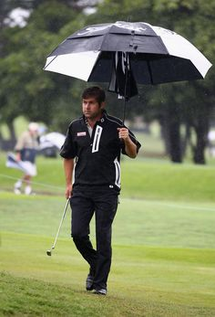 Robert Rock of England holds an umbrella as rain stops play during round one of the South African Open Golf Championships at the Durban Country Club on December 16, 2010 in Durban, South Africa.