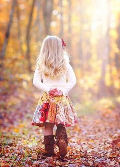 Everything about this picture is just wonderfully cute...her outfit, posture, golden curly hair, the sun shining through the autumn leaves... adorable!
