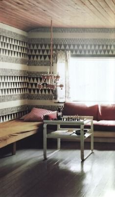 Geometric wall paper, wooden benches and soft pink cushions | Living Room