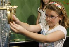 Caroline Hunt places a weight in position to balance a puzzle in the Math Midway exhibit at the Boonshoft Museum of Discovery in Dayton