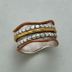 Gleaming metals create beguiling contrasts on our brass and sterling silver spinner ring.
