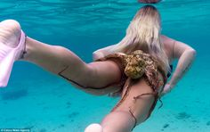 Kathryn Brown, pictured, swims with an octopus stuck to her bikini bottom in the crystal blue waters off the coast of Honolulu