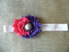 pink and purple shabby flowers are afixed on a very soft elastic headband. In the middle of the flowers is a fancy purple rhinestone embellishment.  Headband fits 3-6 Months