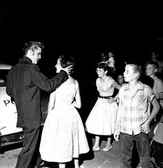 Elvis leaving his home in Memphis , on his way to perform at Russwood Stadium with the local sheriff waiting to drive him and the colonel to the event . july 4 1956
