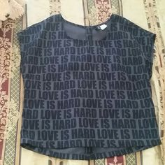 """Top Sort of a cropped style,  says """"love is hard"""" buttoned  down on the back. Divided Tops"""