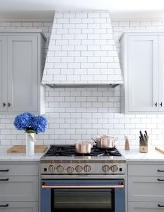 Not your typical stainless steel oven. Love this copper and blue oven with the subway tiled hood and backsplash Design by Threshold Interiors NYC