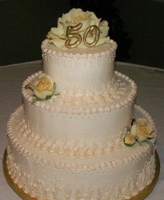 "50th Anniversary - 6, 9, 12 inch round stacked. Iced in off white BC with Ivery hand piped lace work on bottom of tiers.  Airbrushed with gold luster dust.  Silk yellow roses and ""50"" topper made from gumpaste and hand painted gold."