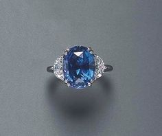 A SAPPHIRE AND DIAMOND RING Set with an oval-cut sapphire, weighing approximately 8.52 carats, flanked on either side by half moon-cut diamonds, mounted in platinum The total weight of the diamonds is approximately 1.10 carats by nora