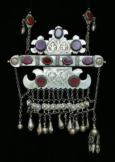 A wedding necklace for a bride from a wealthy Karakalpak family from old Khorezm. Made of silver, probably from melted down Russian and Khivan coins, mounted with nine red glass or carnelian stones and decorated with trefoils.