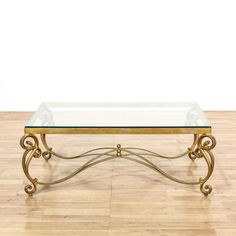 This hollywood regency style coffee table is featured in a durable metal with a shiny brass paint finish. This coffee table has ornate scroll legs with a curved stretcher base and rectangular glass table top. Eye catching table perfect for a glamorous living room! #contemporary #tables #coffeetable #sandiegovintage #vintagefurniture