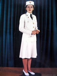 White dress uniform which includes white skirt, black tie, white shoes, gloves and handbag. The white regulation service cap is worn with th...