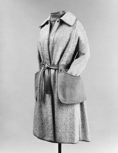 Ensemble by Bonnie Cashin, spring/summer 1973. Wool tweed coat with leather binding and trim for Sills. This photo shows the functional use of the detachable side pockets.
