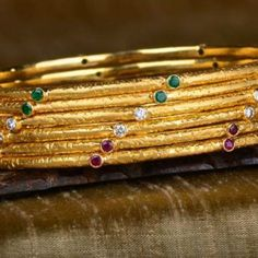 Golden stem bangle set - Nature-inspired set of 6 bangles handcrafted in 18k gold, features emeralds, diamonds and rubies.