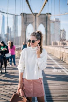 Recreate this look by Gal Meets Glam, by pairing an oversized white sweater with a pink skirt.