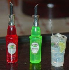 """Miniature """"bottles"""" of Rose's Lime and Grenadine made from Lite Brite pegs, spacer beads and polymer clay."""