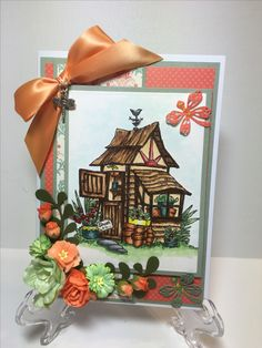 "$9.89. How about a cute card for your gardening fanatic. I colored the garden shed with Copic markers and embellished with lots of flowers from Wild Orchid Crafts. Peachy checkered ribbon with a birds nest charm, and glitter glue to make it sparkle. The card size is 7"" x 5"". It comes with an envelope. I mail my cards in a padded envelope."