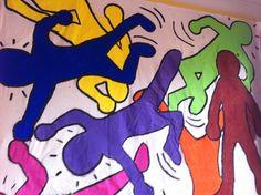 Keith Haring. Samen met de kleuters verschillende posities aannemen en de contouren schilderen.