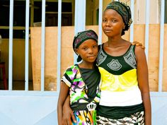 In July 2014 in Sierra Leone, Fatmata Sesay stands with her 11-year-old daughter, Tata, both survivors of Ebola virus disease (EVD), in the city of Kenema, Eastern Province.