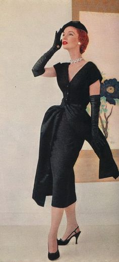 1953 - Style fashion black sheath wiggle dress cocktail hip accent swag gloves shoes hat model magazine color photo print ad 50s couture