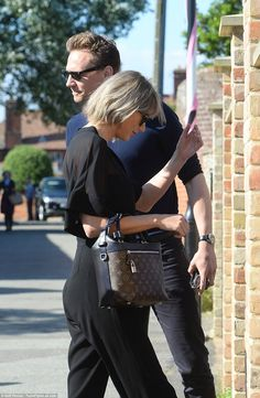 Chivalrous: Tom paused to let Taylor got first as they entered his mother's home...