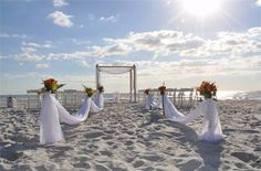 Elegant swagged aisle decor accetned in your selection of floral makes any beach wedding beautiful and created a gorgeous aisle for a brdes arrival to our elegant canopy where her groom awaits ~ A dream come true by Simple Elegant Weddings