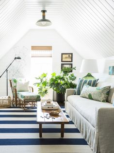 A blue and white striped rug anchors the room in nautical style, and echoes the texture of the country home-inspired shiplap walls and ceiling.