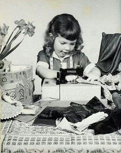 A little girl uses a miniature sewing machine, ca. 1950's.