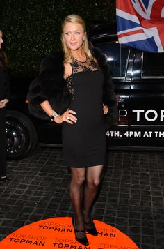 Paris Hilton makes another showing, this time in a black dress with black pantyhose.