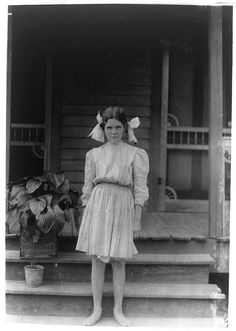 Myrtle Bagwell, one of the youngest spinners in Spartan Mills, Spartanburg, S.C., standing on porch steps. Lewis Hine, photographer. Photographic print. 1912 May.