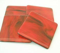 Coasters of transparent and red opal streaky glass fused on a black opal base panel. Size approx 10cm x 10cm