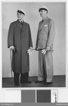 """Studentmode 1935. Två unga män i studentmössor och med studentkäppar. Den ene bär en ytterrock med dold knäppning, den andre en ljus, dubbelknäppt kostym. Nordiska Kompaniet. Text med blyerts på baksidan: """"MH 1935"""". Fotograf: Erik Holmén, 1935."""