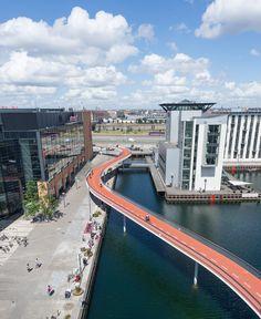 The Bicycle Snake. Bicycle Bridge, Copenhagen, Denmark. Competition: 2010, 1st prize, Completed 2014. Length: 230 m, Width: 4.6 m, Height difference between Havneholmen and Fisketorvet's main entrance: 5.5 m, Column distance: 17 m. Client: The City of Copenhagen. Architect: DISSING+WEITLING architecture. Landscape: Marianne Levinsen Landskab. Engineer: Rambøll (DK). Contractor: MT Højgaard (DK). Light Design: lightconstructor (DK).
