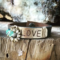 Leather cuff, stamped silver metal, love, sunflower charm.  www.ahavadesign.com
