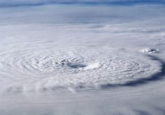The storm clouds of Typhoon Bopha form a spiral far below the International Space Station