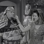 Vernon Dent getting his cheek pinched by the slave girl in the Three Stooges short, Mummy's Dummies