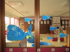 Papier blauw schilderen met handen, daarna suiker en/of zout opstrooien en walvisjes uitknippen