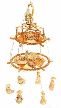 This corn dolly, of the 'chandelier' type, was made by Alec Coker. It consists of two flat hexagonal bases made of parallel corn stalks, each of which is surrounded by a spirally woven circle. It was made to display some small plaited grass nativity figures from Ecuador. (MERL/86/133)