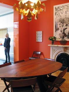 """The dining room features an asymmetrical table and brilliant orange color on the walls. The previous interior colors made the home feel like a gallery space for the furniture. """"Before it was all white,"""" the owner says. """"But we wanted to add more atmosphere and mood. We worked on the colors really hard, making boards for all of our finishings."""""""