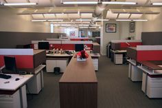 Open office featuring fabric-wrapped acoustic wall & cubicle panels with floating ceiling clouds & baffles