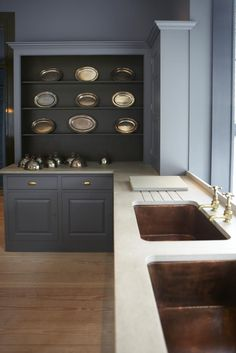 The dark interior of these shelves. copper sinks , brass fittings...it all worsPlain English