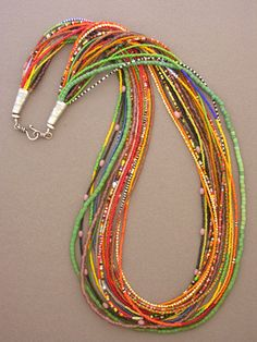 This colorful 16-strand necklace is made of thousands of tiny antique  beads from a Fulani woman's waist belt. The Fulani are a nomadic tribe  from Mali, and these belts were typically worn under the women's  skirts. The necklace can be worn long (as shown), or can be double-  wrapped around the neck. Sterling silver cones and  a sterling silver hook and eye clasp that was handmade in Sri Lanka.