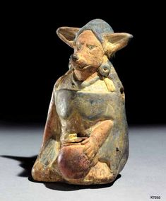 Maya. clay. paint. height 12.2 cm. Figure in the form of a female canine holding an olla with lid.