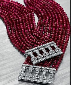 A Pair of Art Deco Ruby Bead and Diamond Bracelets, by Cartier Designed as nine strands of ruby beads, joined by a square and single-cut diamond openwork clasp of geometric design, mounted in platinum, circa 1925, 7 ins., with French assay mark and maker's marks Signed Carter, France