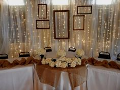 Head Table Backdrop rental 20'W x 10'H, draped in chiffon, fairy lights and rustic picture frames. Custom Pipe & Drape structure offered by Moments In Time Wedding & Event Rentals, 406.208.9549.