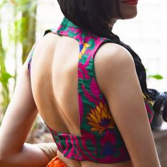 DESCRIPTION: An alluring chinese collared blouse with a cutout trapezoid back for added interest.FABRIC:  Body - Green dupion with yellow pink and violet threadwork with twines and lotus motifsCollar - Emerald green raw silkPRODUCT CODE: HOB-MR15-CH-01CARE: Dryclean only