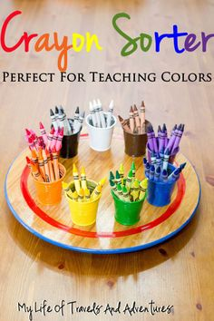Toddlers can learn colors by sorting crayons in matching cups.
